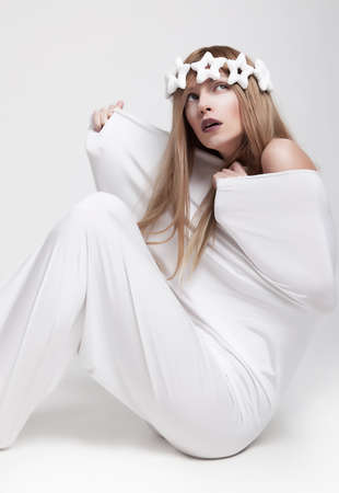 Dramatic pose - young girl in white crown and clothes sitting