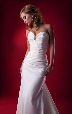 Sensual attractive blond hair bride posing over red background. Studio shot, series of photos Stock Photo