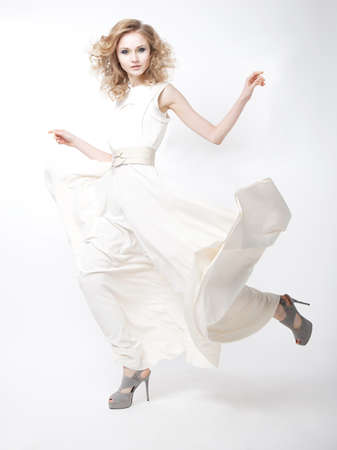 sexiness: Lovely happy young female blonde hair fashion model in waving white dress. Series of photos