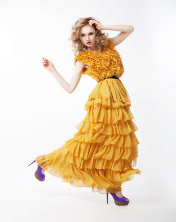 Pretty happy active female blond hair woman in yellow dress posing. Fashion style. Studio shot