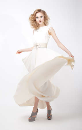 Fashion style - luxurious young woman in light flying dress posing in studio. Series of photos photo