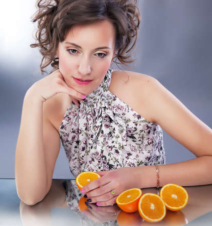 dishy: Sorrow - pretty young female with fresh halves of oranges reflects in mirror. Series of photos Stock Photo