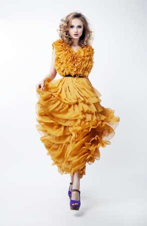 Schöne weibliche blonde Mode-Modell im gelben Kleid isoliert über weißem Hintergrund