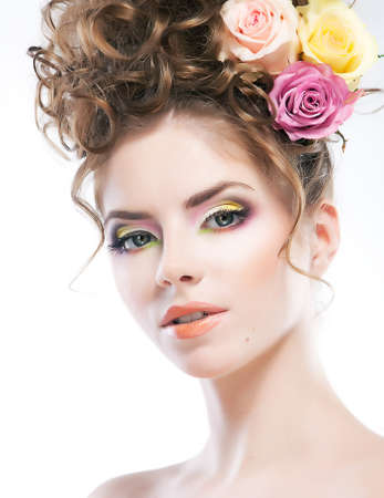 Beautiful face of young woman, clean skin. Beauty girl - long curly brown hair with flowers and bright  makeup photo