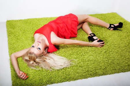 flirtatious: Pretty young woman blonde resting in green carpet