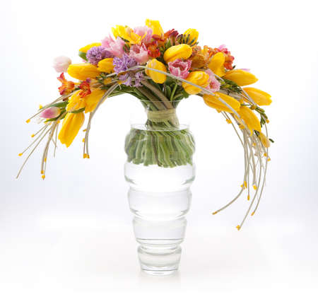floral arrangement: Floristics - colorful vernal flowers bouquet arrangement in vase isolated on white
