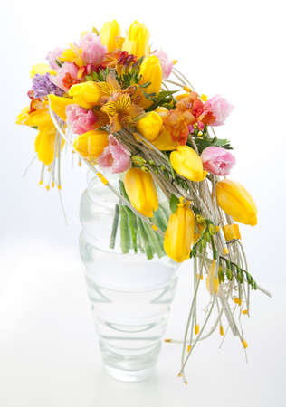 floristry: Floristry - colorful flower bouquet arrangement centerpiece in transparent vase isolated on white background Stock Photo