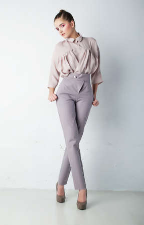 Fashion model female in trousers and shirt posing photo