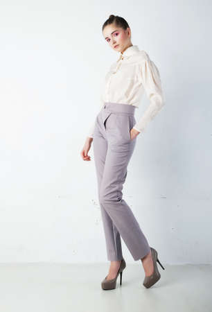 Young pretty brunette woman in white shirt and blue trousers in studio  Fashion style photo
