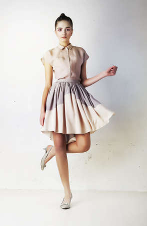 Fashionable young female in contemporary short dress  Studio shot