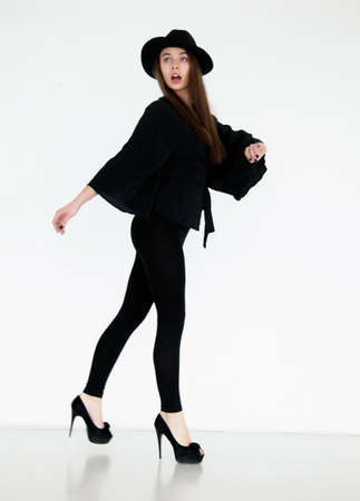 Beautiful young model girl in black hat on the white background  Fashion photo photo