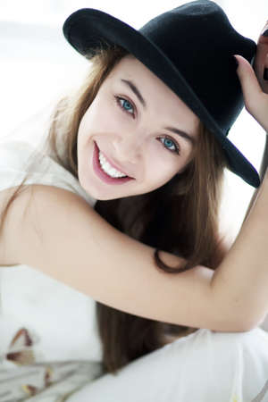 Portrait of a sexy smiling brunette woman wearing a black retro hat photo