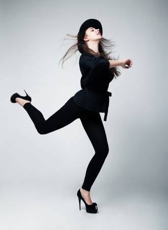 Retro style  Fashion model girl in black running in studio photo