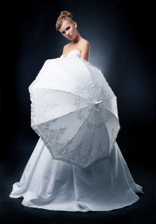 Wedding style  Fashion model blonde woman in bridal dress with umbrella Stock Photo - 12816674