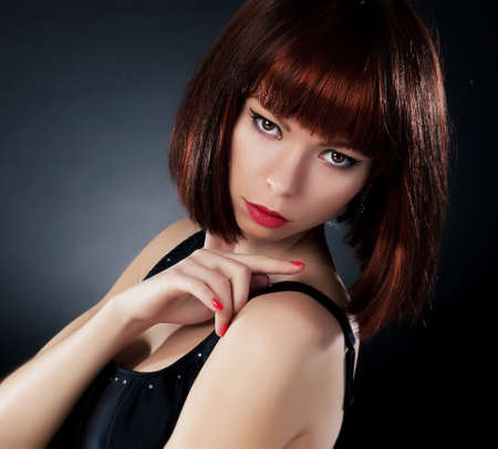 Beauty  Beautiful red hair woman over dark background photo