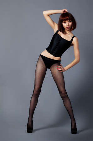 Beautiful fashionable woman in wig and pantyhose posing photo