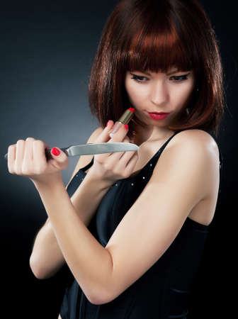 Beautiful woman with knife and lipstick  Sensual sexuality gaze  photo