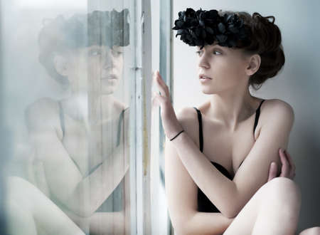 Pretty woman in black wreath of flowers looking through the window photo