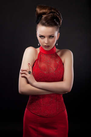 Strict beautiful business woman in red dress isolated on black background photo