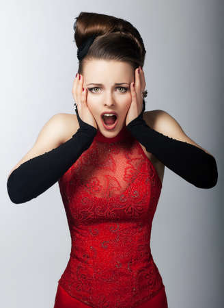 surprised face: Astounded young pretty girl in fashion red dress - studio shot