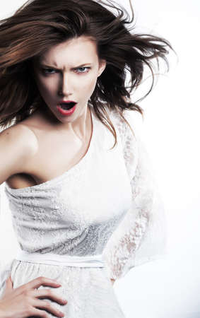 Young angry woman brunette with waving hair screaming  Studio shot photo