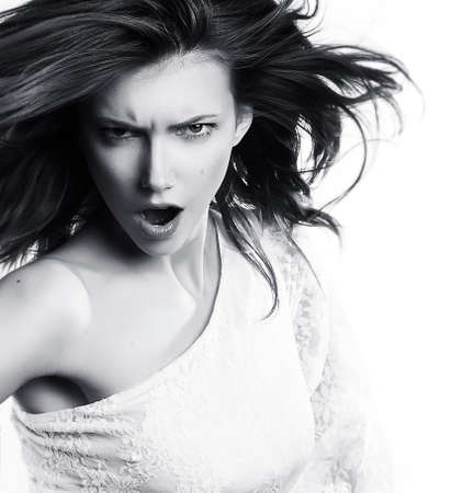 Young woman screaming on white background - black and white photo photo