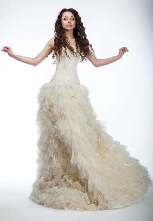 Happy beautiful woman with long curly hair in luxurious wedding dress posing Stock Photo - 13344684
