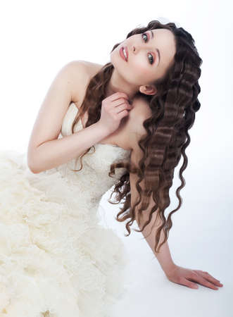 Portrait of beautiful young bride with wedding hairstyle - sitting over white background photo