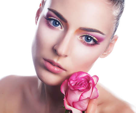 Beautiful young woman with pink rose close up beauty portrait