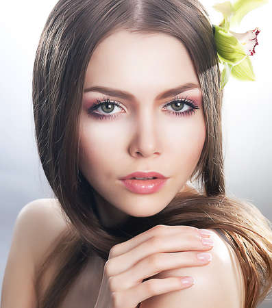 nude woman sexy: Skincare of young beautiful woman face with fresh flower - orchid