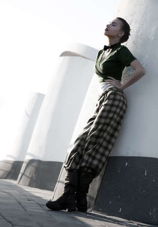 Beautiful young woman in checkered trousers stand leaning on city walls photo