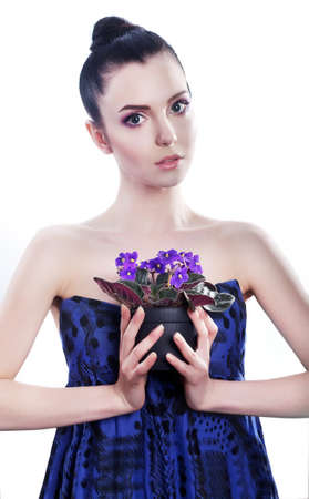 Beautiful young woman with flowers in blue dress posing in studio Stock Photo - 13577731