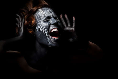 warrior tribal: Art photo of a stressed ethnic woman with black painted mask on face and tattoo Stock Photo