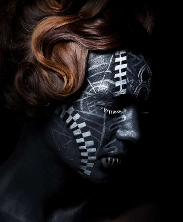 ceremonial make up: Sad woman with black painted face in carnival mask Stock Photo