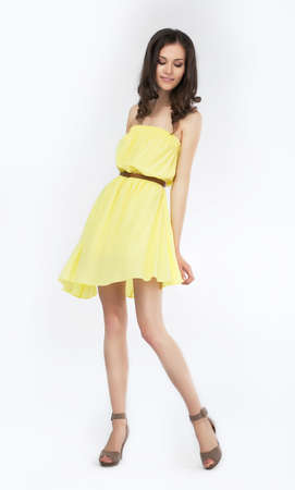 wind dress: Trendy young woman in funky yellow dress smiling against white background
