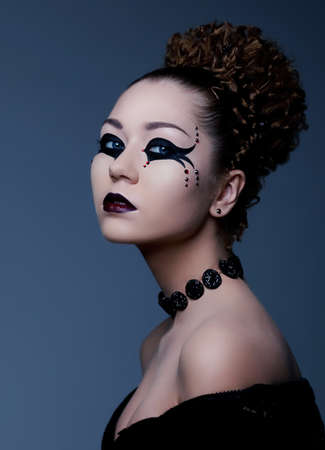 Fashion style portrait of a woman with dramatic theatrical makeup on her face photo