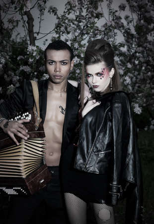 Two punks - fashion girl and boy in black clothes with accordion photo