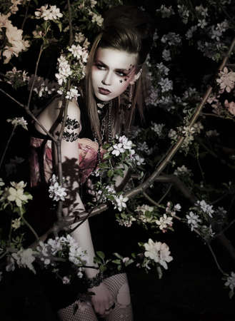 Flowers  Pretty girl with stylish makeup posing among blooming apple trees photo