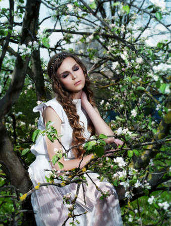 Young sexy woman among blooming apple tree with flowers photo