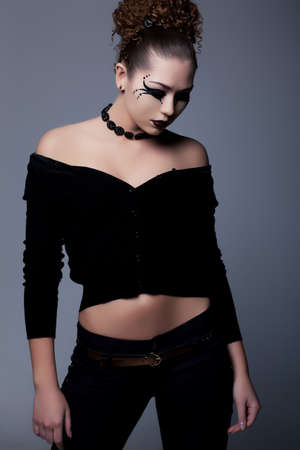 Young slim lady in black with creative makeup posing photo