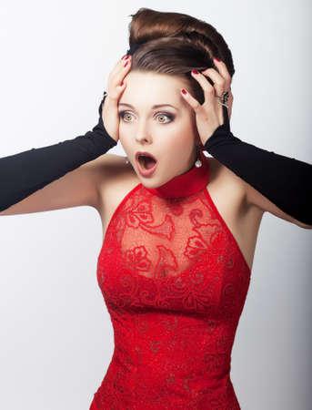 gente loca: Retrato de mujer sorprendida emocional en vestido rojo aislado