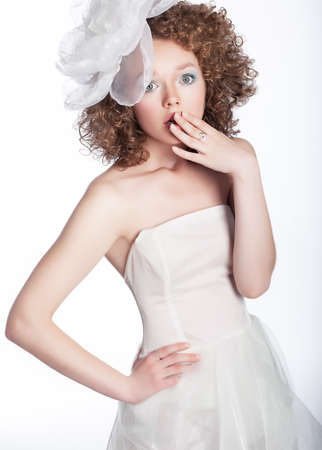 Pretty young surpised woman in white wedding dress isolated  Studio shot photo
