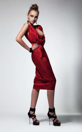 Beautiful fashion woman in red dress posing in studio photo