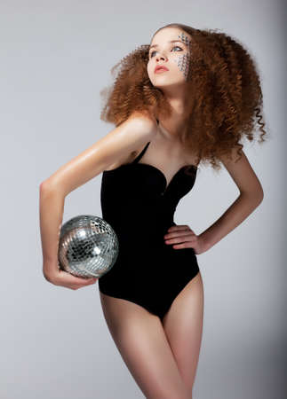 Sexy redhead female in black body with brilliant mirror ball posing Stock Photo - 14373409