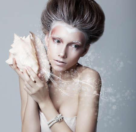 letras musicales: Hermosa chica con concha de mar en sus manos que fluye letras de m�sica Foto de archivo