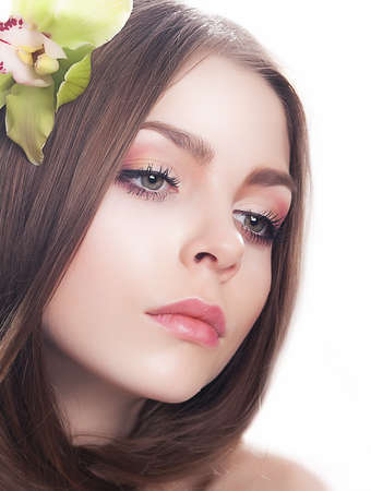 Young beautiful woman face with fresh orchid flower close-up portraut  Clean healthy skin Stock Photo - 14402211