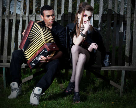 Couple young people - black man and white woman sitting on bench against the fence Accordion Countryside Serenade Stock Photo