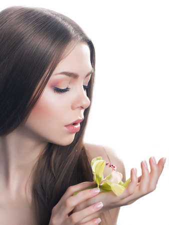 Beautiful tranquil pretty girl holding orchid flower in her hands  Beauty purity model photo