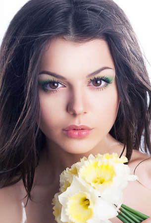 Beautiful girl face closeup with spring flower - daffodil narcissus photo