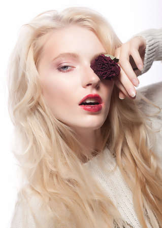 Blonde girl with beautiful hair and red rose  Birthday or valentines day concept photo